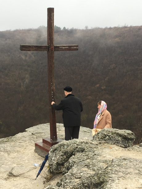 A man places a prayer in the cross above Saharna Monastery and its quarry